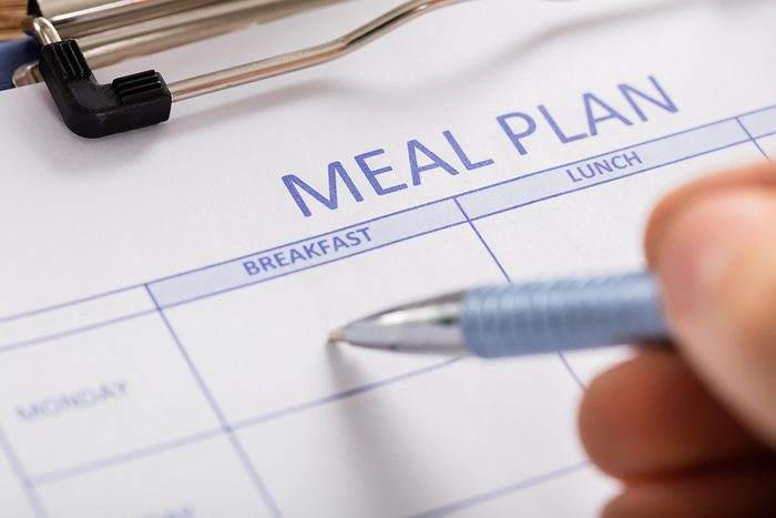 Someone filling in a day on a meal plan calendar