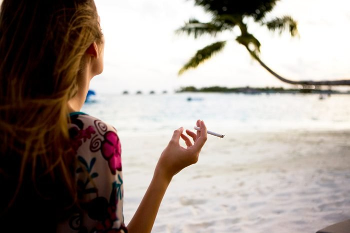 rear view of woman smoking on the beach