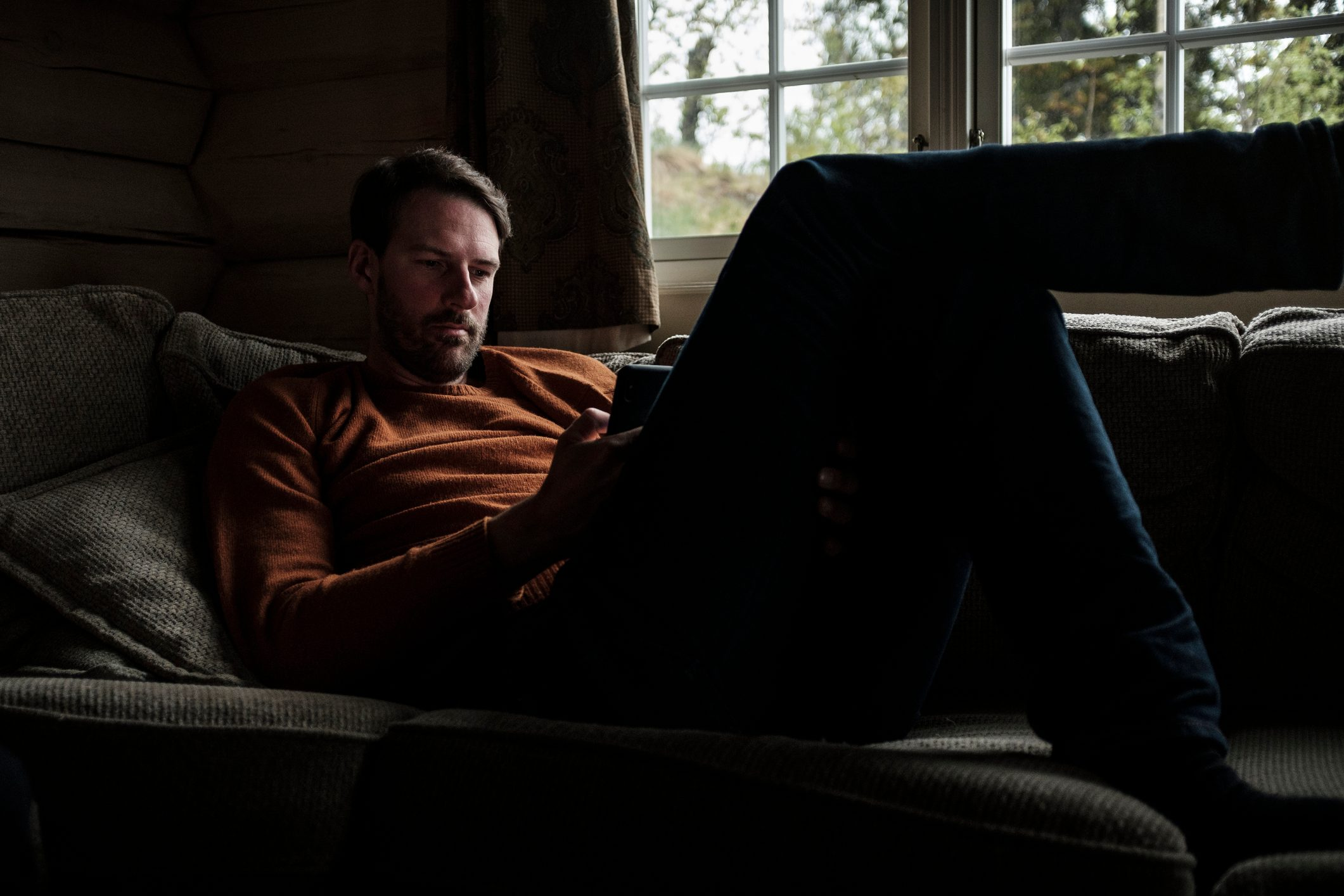 man sitting on sofa looking at smartphone device