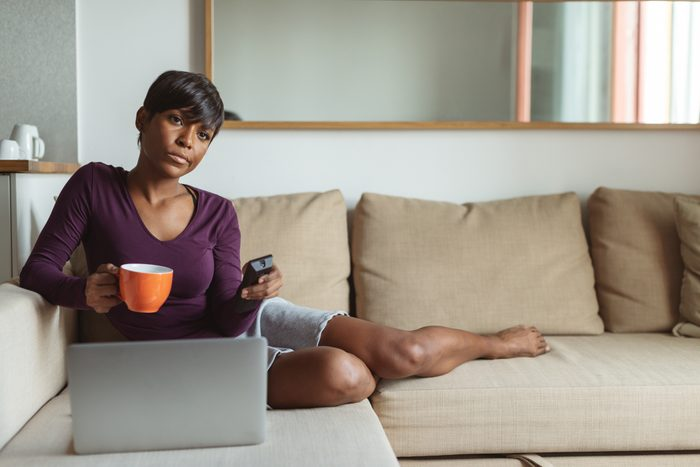woman watching tv and using laptop on couch at home