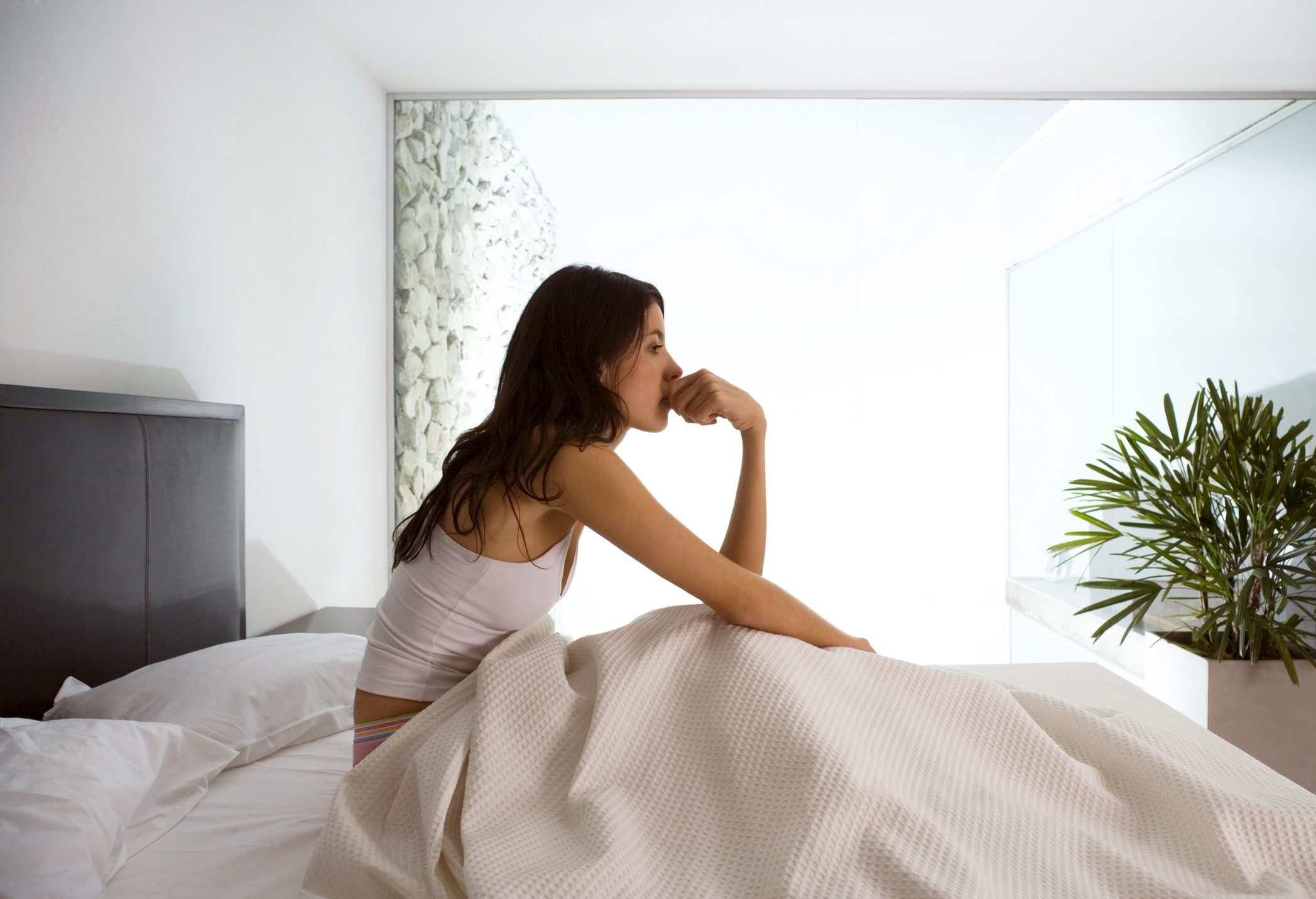 woman sitting up in bed biting nails