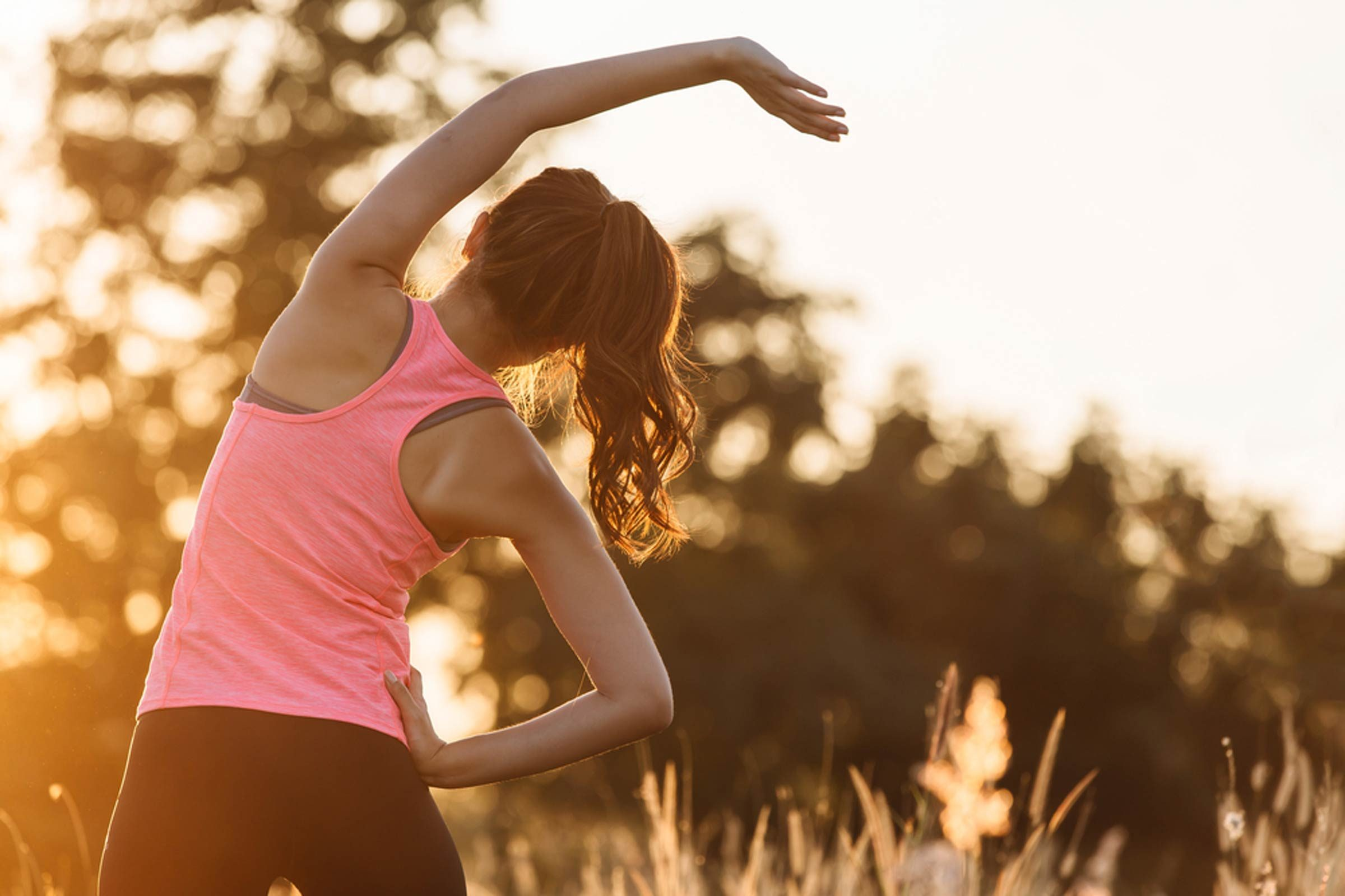 Woman in a pink tank top stretching outdoors.