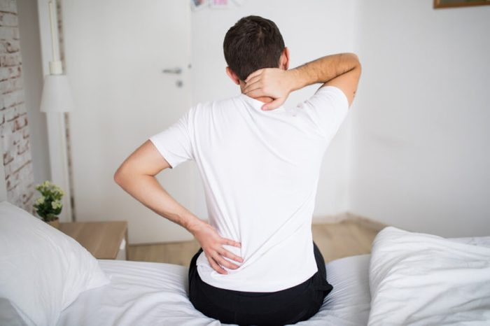 Man sitting on his bed, holding his back and having intercostal neuralgia.