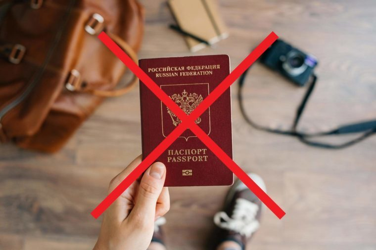 A person holding a passport with an X through it.