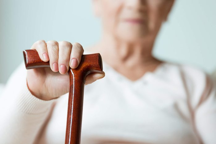 senior woman with hand on a cane