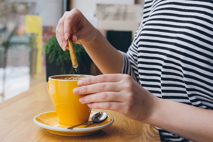woman putting sweetener in cup