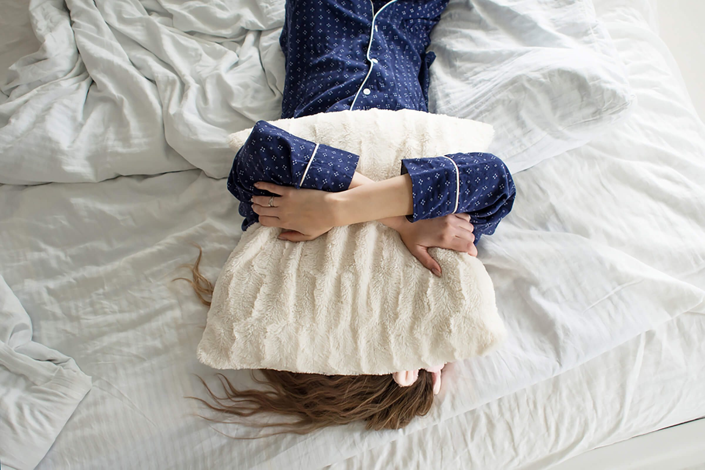 woman with pillow over her face in bed