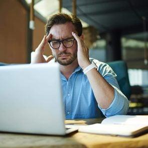 Businessman feeling headache while doing distance work in coffee shop