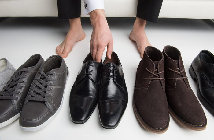 man chooses which pair of shoes to wear
