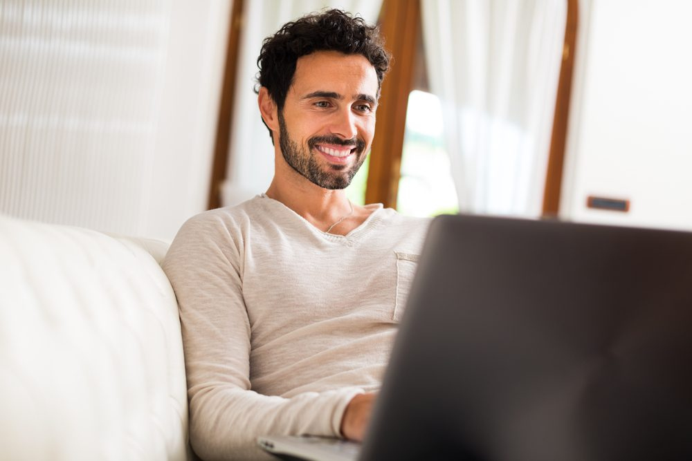 Man using a laptop while sitting on the couch