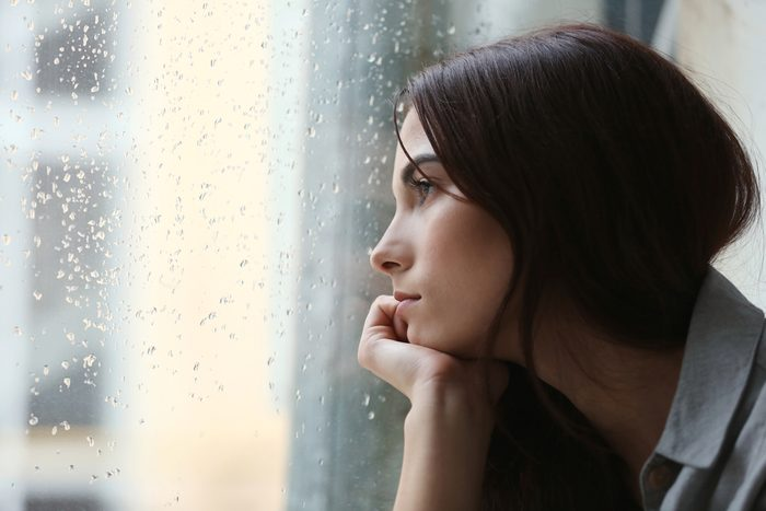 Depressed young woman looking out rainy window