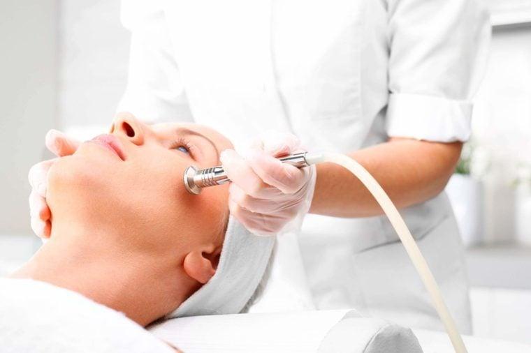 skin esthetician apply facial device on woman