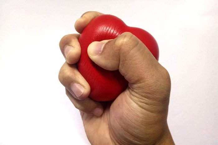 hand squeezing red stress heart