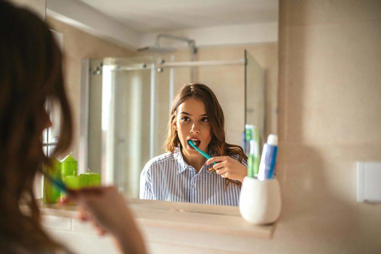 woman brushing teeth while looking in mirror