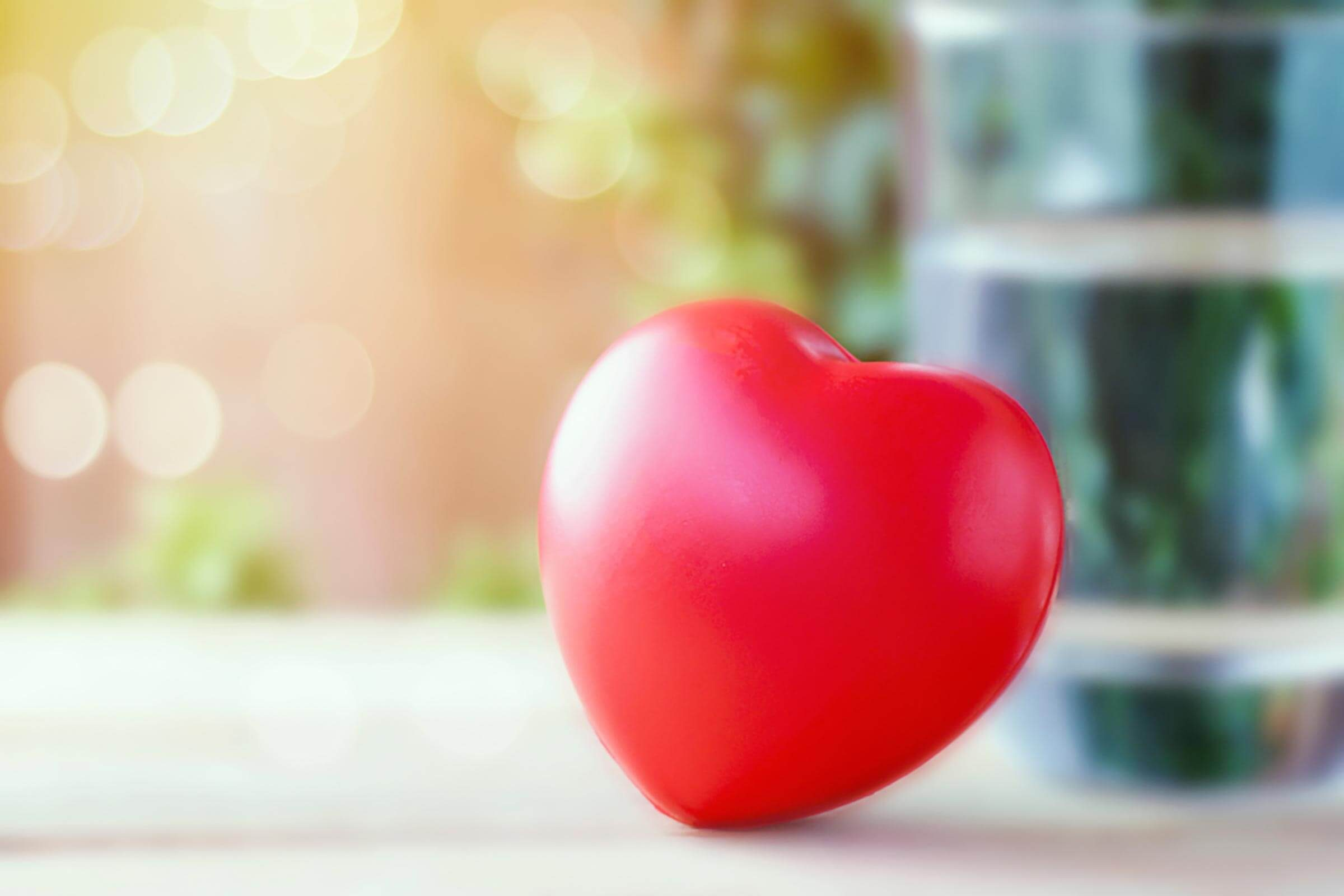 toy heart leaning against glass of water