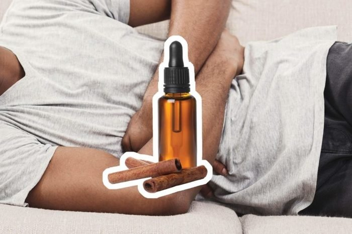 Cinnamon oil over a reclining man holding his stomach