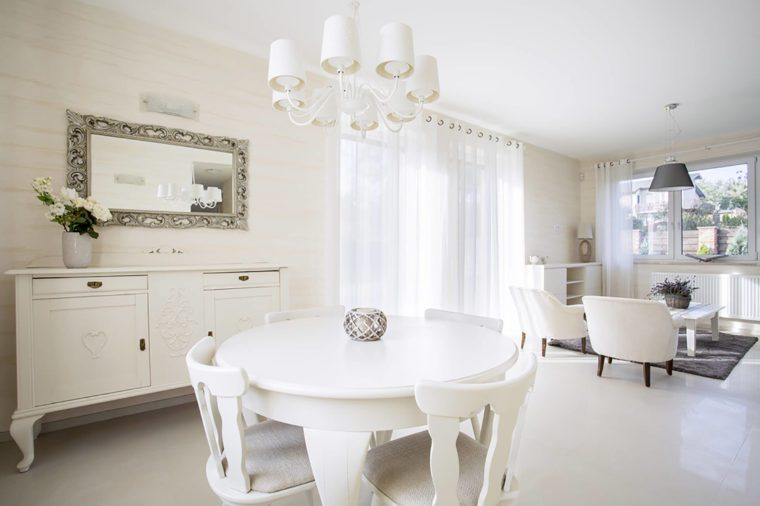 white dining table with white chairs in a white room with a mirror