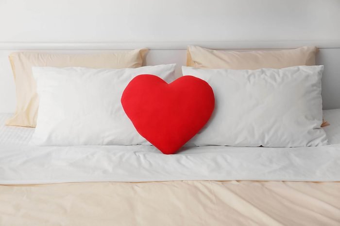 red heart pillow on bed