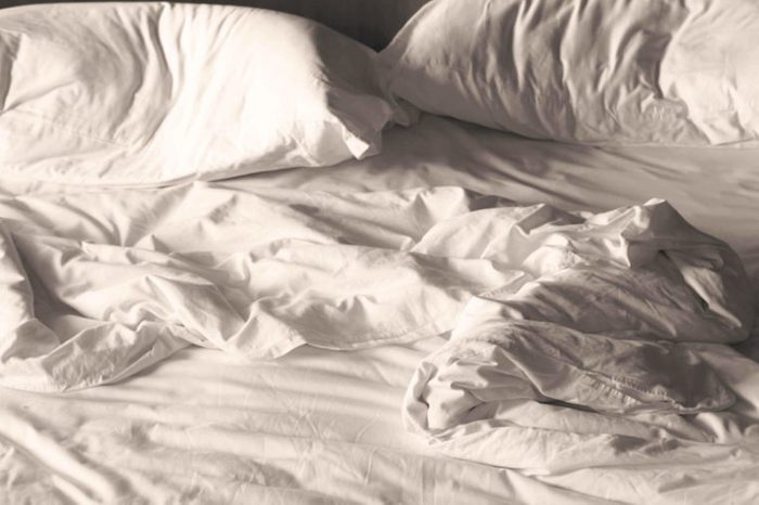 A messy, unmade bed with white sheets and pillows.