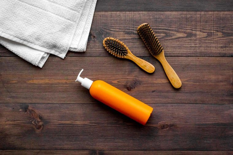 hair brushes, towel, and pump bottle on a dark wood surface