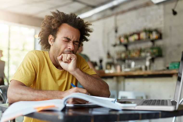 Man yawning at table with book and computer
