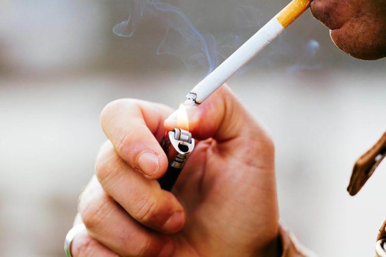 man lighting a cigarette