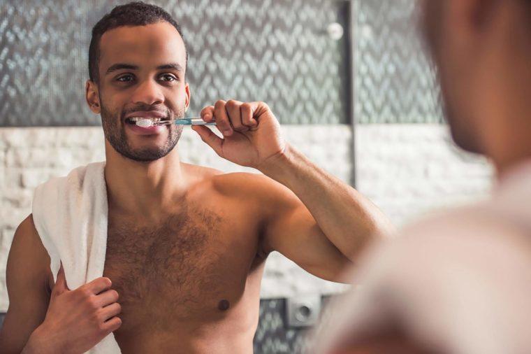 shirtless black man brushing teeth in mirror