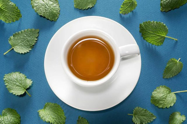 cup and saucer of tea with mint leaves