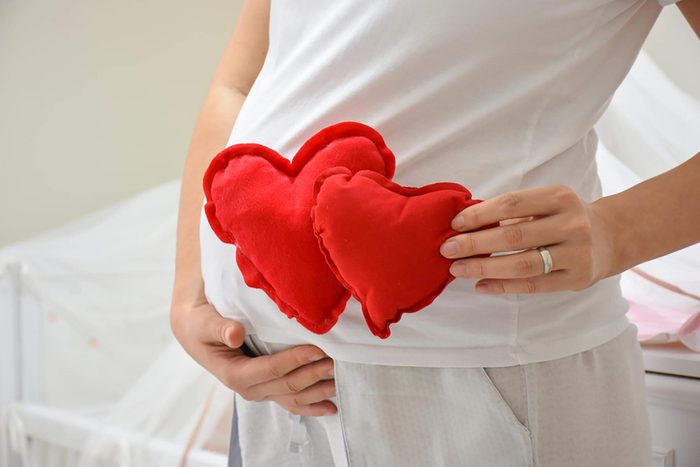 pregnant woman holding heart-shaped pillows by belly