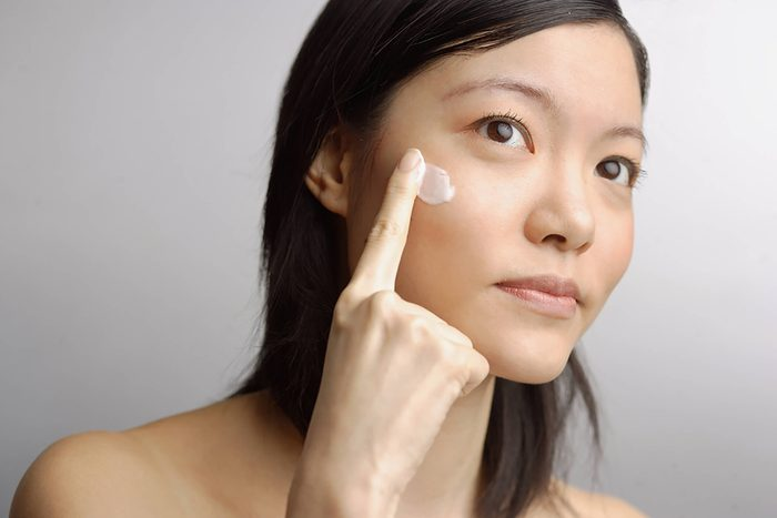 Woman putting cream on face