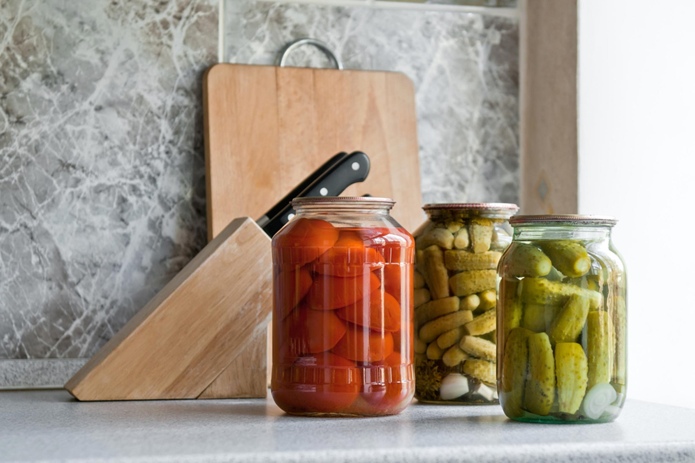 jars of pickled vegetables on a kitchen counter