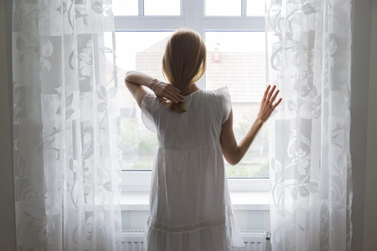 sad lady standing by a window