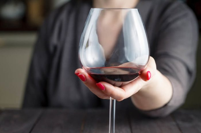 woman drinking alcohol on dark background. Focus on wine glass