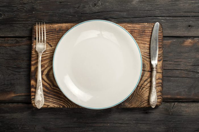 White empty plate with fork and knife on a old wooden board on a dark wooden background, top view