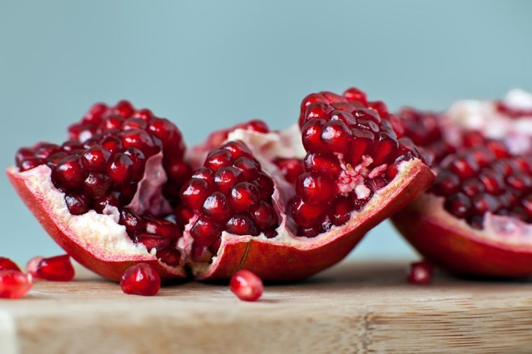 Pomegranate split open on a wooden cutting board