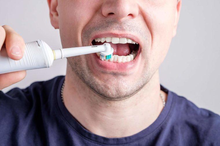 man using an electric toothbrush