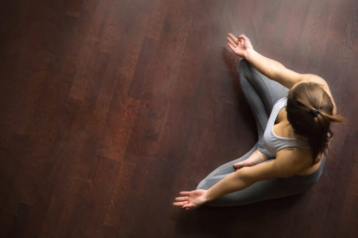 Young yogi woman practicing yoga, sitting in Half Lotus exercise, Ardha Padmasana pose, working out, wearing sportswear, grey pants, indoor, home interior, wooden floor, high angle view, copy space