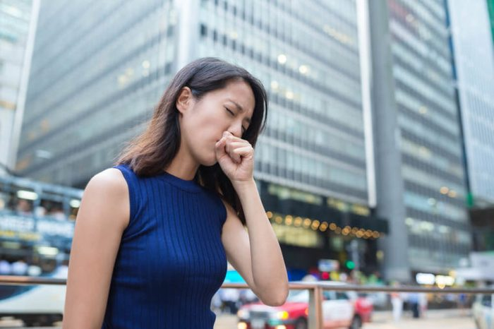 business woman in urban setting outdoors, coughing into her fist