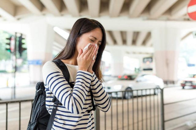 Asian Woman sneezing in into a tissue