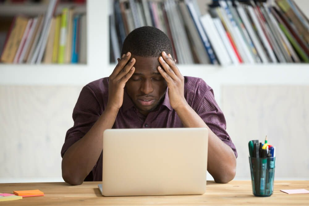 Frowning man looking at computer with head in hands