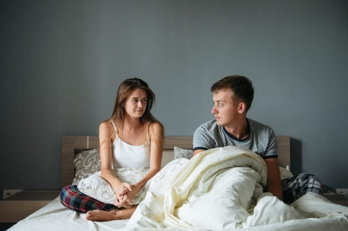 Drowsy man and woman sit on bed