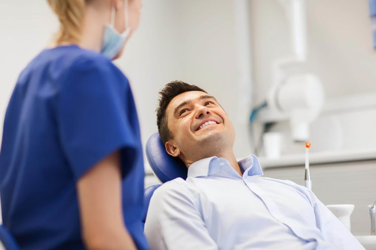 patient in dental chair smiling at Dentist