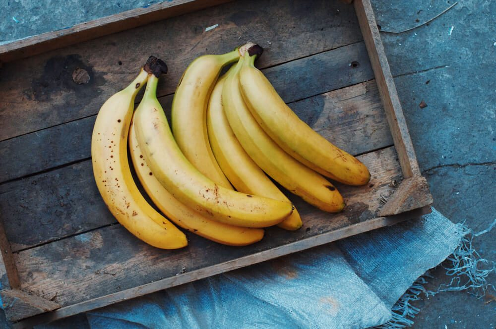 ripe yellow bananas in a wooden tray