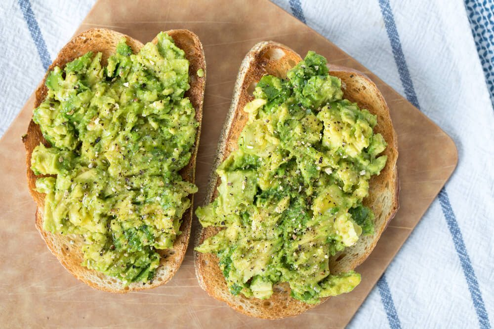 Heart healthy diet; Over head avocado toast on slices of toasted French loaf bread topped with ground lemon pepper and sprinkles of kosher salt on wood cutting board on top blue and white striped linen cloth