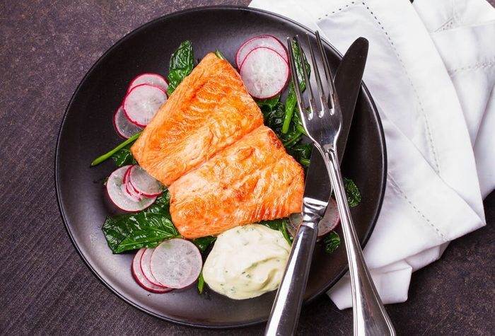 heart health diet; Broiled salmon with radish and spinach, served on black plate. View from above, top studio shot