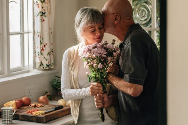 senior couple in kitchen husband giving wife flowers