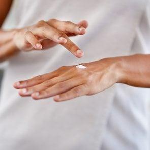 woman applying moisturiser to her hands psoriasis skin remedy