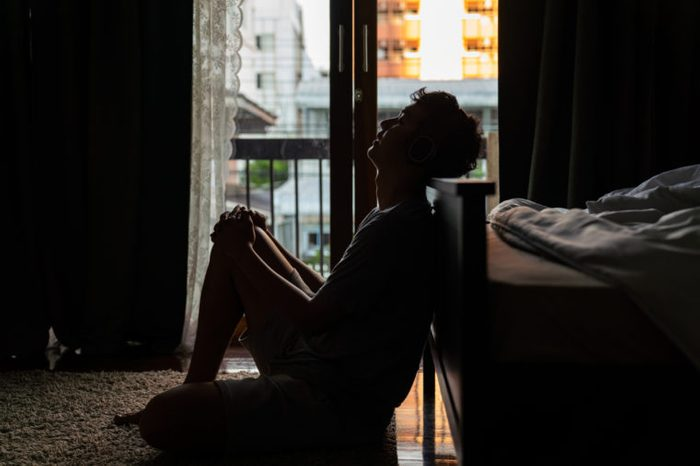 silhouette of a man sitting at the foot of the bed