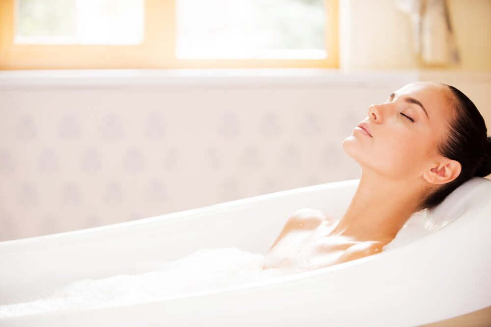 Woman keeping eyes closed while enjoying luxurious bath