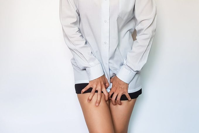 Woman reaching toward her groin because of itching vagina